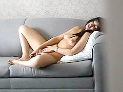 Cute girl discreetly filmed by voyeur rubbing herself off on the couch hidden cam