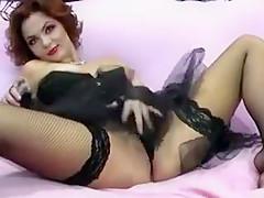 Classy redhead in black lingerie sensually fingers her shav