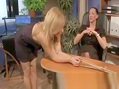 Blonde beauty tied down to desk by brunette domina