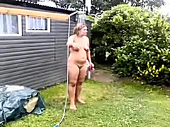 Aged fat wife naked on the backyard washing with a hose